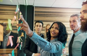 Businesswoman leading collaboration session with postit note board, possibly engaging the Board and CEO.